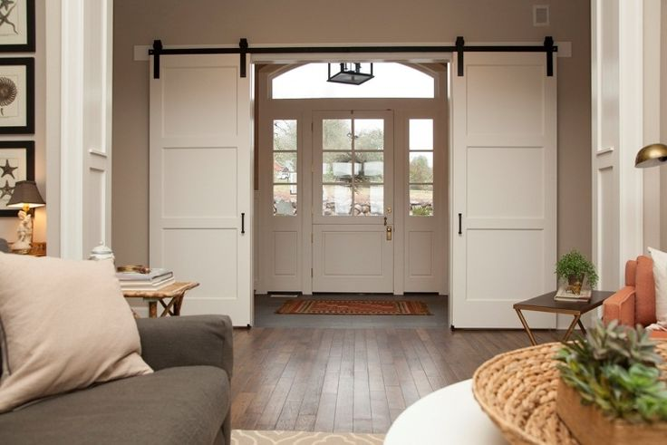 Schiebetüre aus Holz separieren den Eingangsbereich vom Wohnzimmer