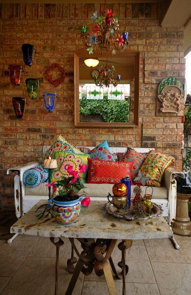Eclectic. ~~~Love the table base. Nice collection of pillows. I do not like the rest of this room. Needs rug, wall arrangement too high, mirror should be hung horizontally, lower chandelier a bit.