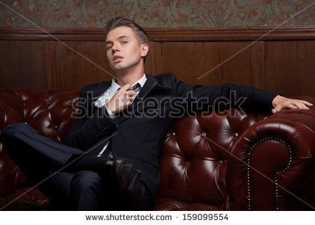Glamorous young man in a suit sitting on a sofa