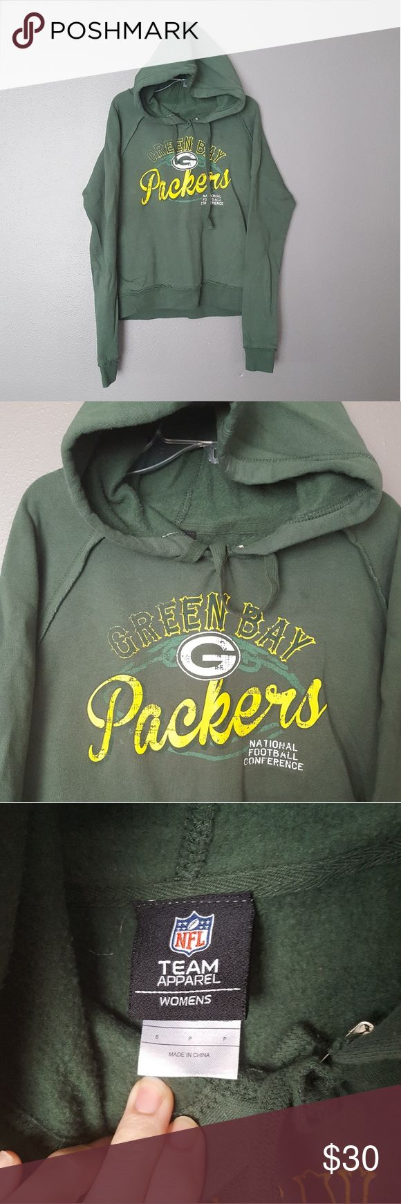 """《NFL Team Apparell》Greenbay Packers Hoodie Worn once, washed once. NFL Team Apparell Greenbay Packers hoodie. Size small, true to size.  Green hoodie. Chest design is distressed, not from wear.   Pit to pit 21"""" (42 around) Top to bottom hem is 23""""  Reasonable offers considered.  Tags: green, yellow, Green Bay, Packers, hood, casual, comfy, sweats, football, NFL, national football conference NFL Team Apparell Tops Sweatshirts & Hoodies"""