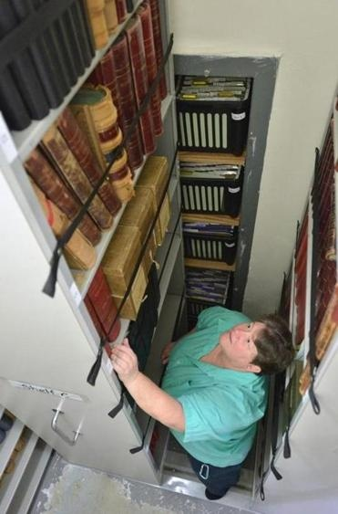 Reading Town Clerk Laura A. Gemme stands among stacks of old records being converted into online data.