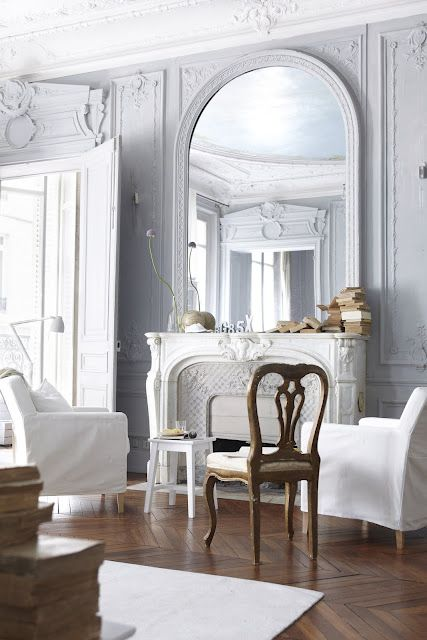 White fireplace, light grey walls, moldings and oval mirror.