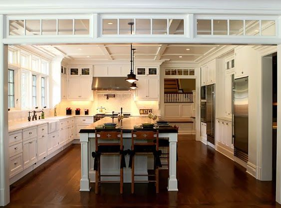 Transom windows define the space between a kitchen and living area.  White, marble, stainless kitchen.