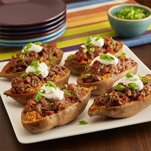 Stuffed sweet potatoes are 'filled' with prepared pulled pork in barbecue sauce with tomatoes, then topped with sour cream and green onions for a quick weeknight main dish
