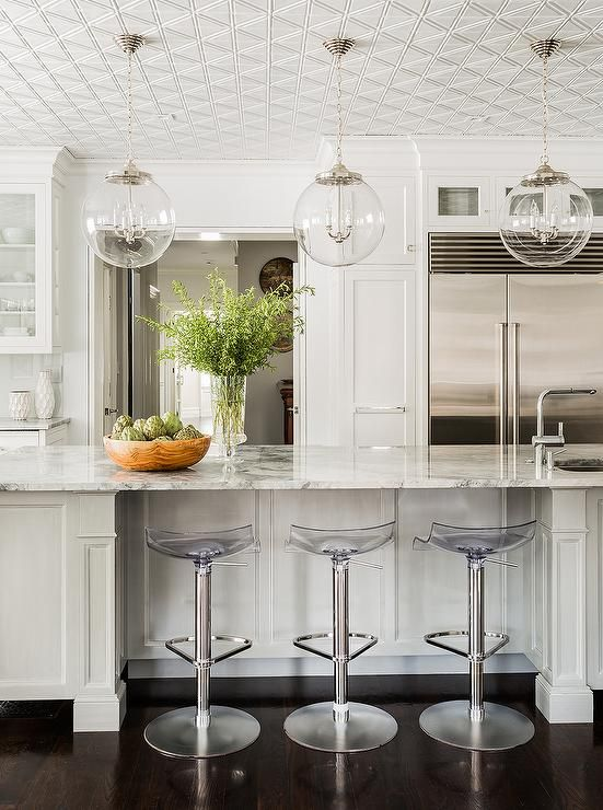 Amazing kitchen features three Regina Andrew Large Pendants suspended from a diamond pattern ceiling over a long center island lined with acrylic adjustable bar stools with footrests.