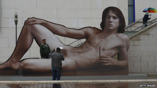 Gallery-goers pose with supersize poster for Nude Men exhibition