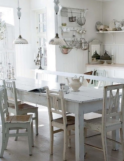 White vintage farm house table with chairs and a bench.