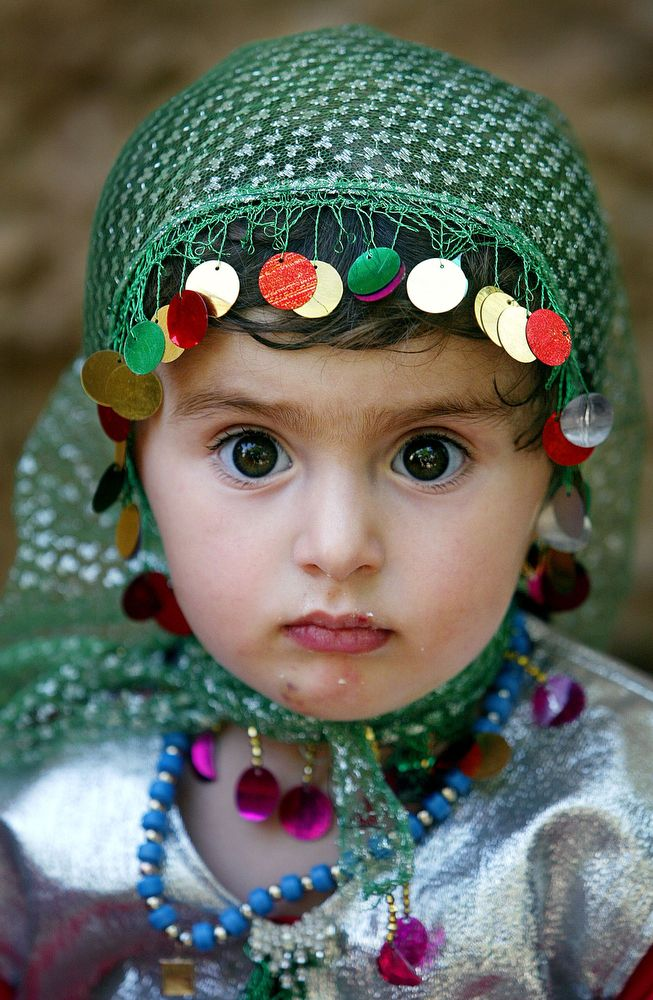 A Kurdish girl, Leiwan, 2, attends a traditional wedding celebration June 15, 2003 in Bakochek, Iraq. Saddam Hussein's regime killed an estimated 180,000 Kurds from 1988-1991 in a genocidal campaign involving both chemical and conventional weapons. (Photo by Mario Tama/Getty Images)
