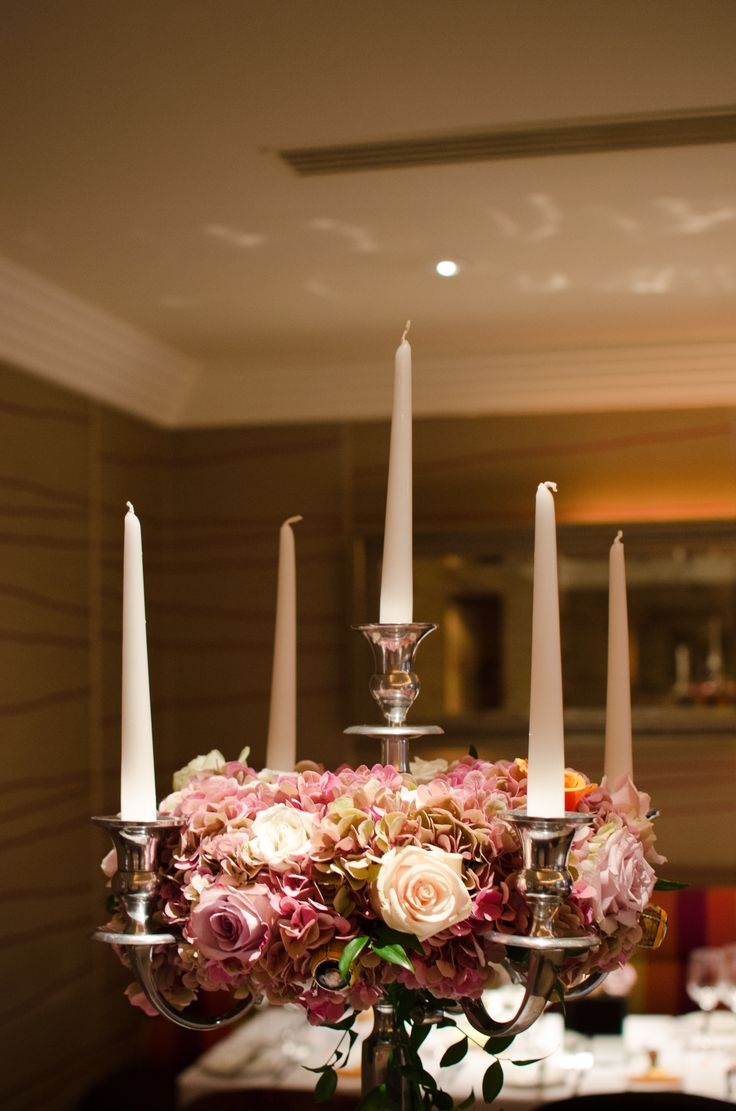 Silver candelabra table arrangement with a ring of hydrangea and roses