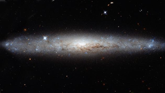 Hubble 'desempolva' una hermosa galaxia espiral. La combinación de varias fotografías de perfil de la galaxia espiral barrada NGC 4183 facilitó a los astrónomos la primera impresión visual completa y detallada de este objeto celeste conocido y catalogado desde 1778.
