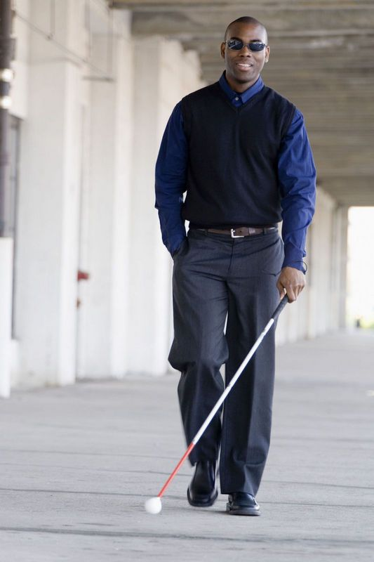 Blind young man walking on the sidewalk, with  a white cane