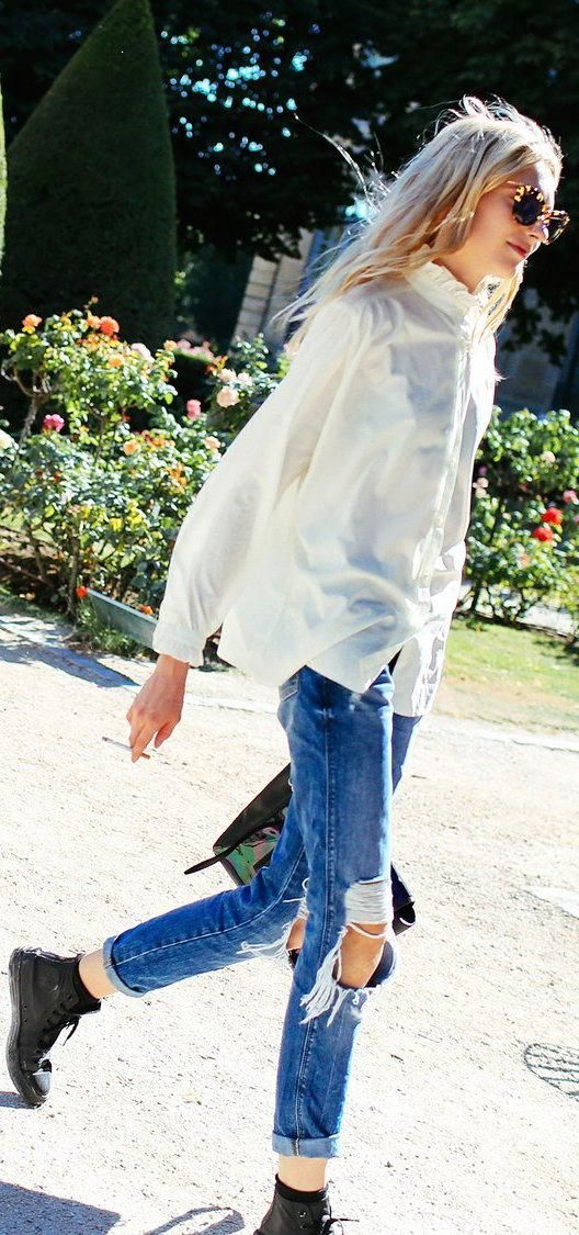 Valery Kaufman in a white button-down blouse and ripped boyfriend jeans