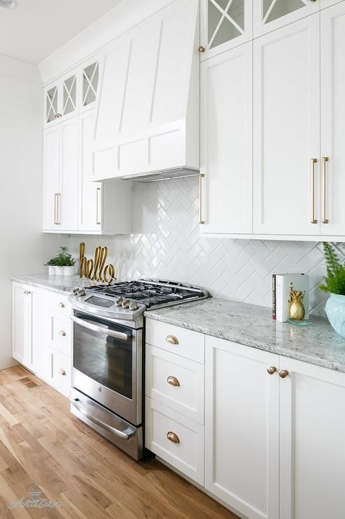 A stainless steel oven range sits against white herringbone backsplash tiles beneath a white paneled hood flanked by white shaker cabinets adorning champagne gold pulls stacked beneath x-front glass display cabinets.