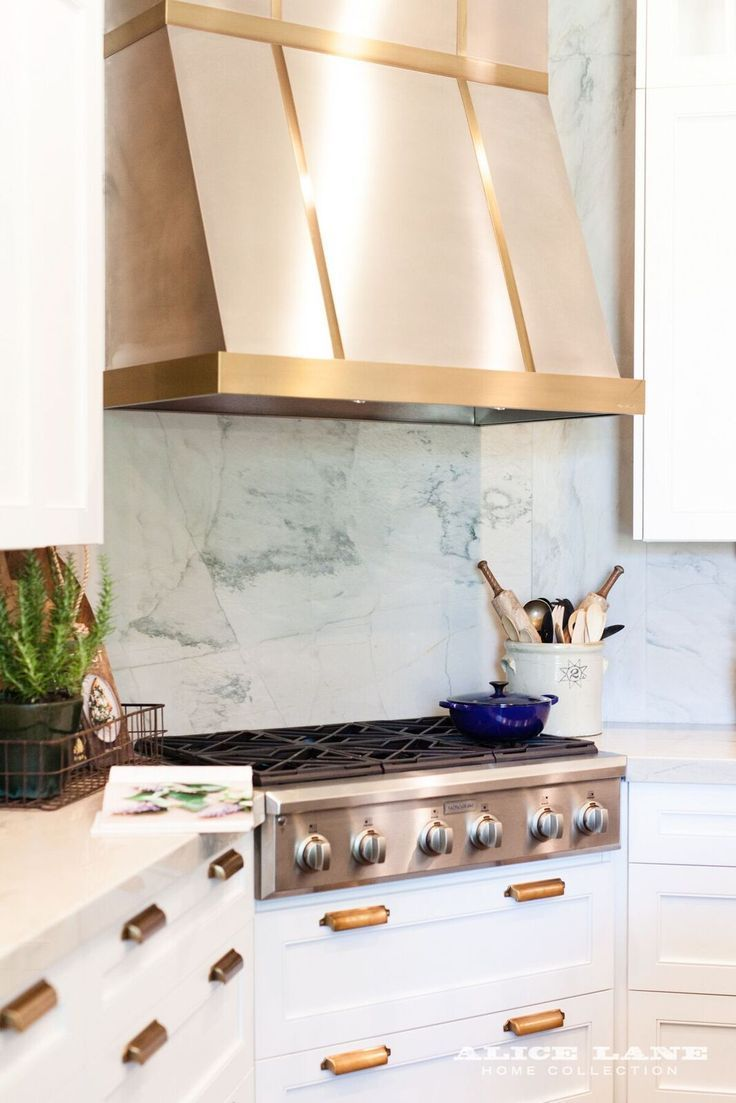 Gold range hood and Quartzite in this All American Kitchen  Designed by Alice Lane Interiors Photo by @aceandwhim