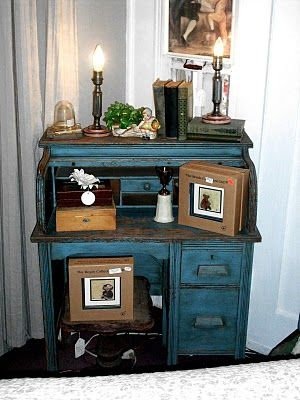 I like this idea - in an off-white; possibly leaving the desk top and inside cubbies the original wood finish and embossed wallpaper (painted an off-white as well) on the inset wood side panels