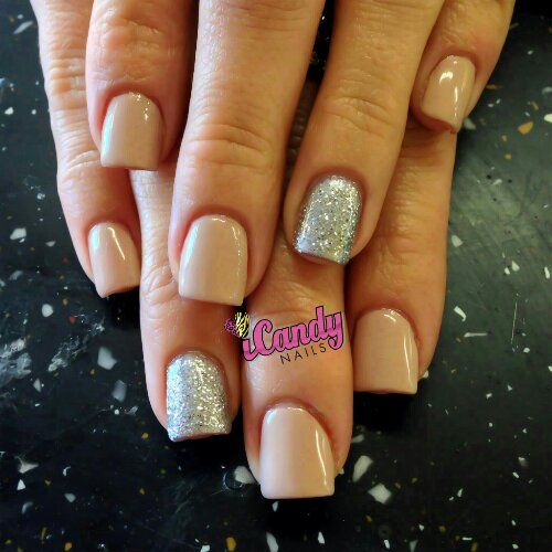 Nude nails with sparkle accent nail.