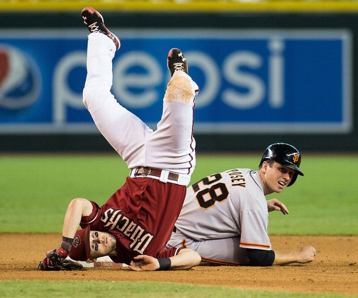 Diamondbacks second baseman Chris Owings takes a tumble as Giants first baseman Buster Posey slides into him during a baseball game, Thursday Sept. 17, 2014 in Phoenix. (AP Photo/The Arizona Republic, Dominic Valente)