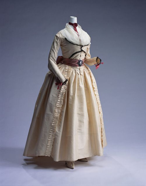 """A gown for Caro or Meagan in Spring Fires. Around the time of French Revolution, during the transition period from the Rococo style silk dresses to plain cotton dresses after the Revolution, simple & lovely gowns like this were in vogue. This dress made of light plain silk taffeta has a """"compères"""" style double front bodice. The sole decoration to this dress is black lace trim.  When wearing this dress, a thin """"fichu"""" was placed in the large opening at the top of the bodice."""