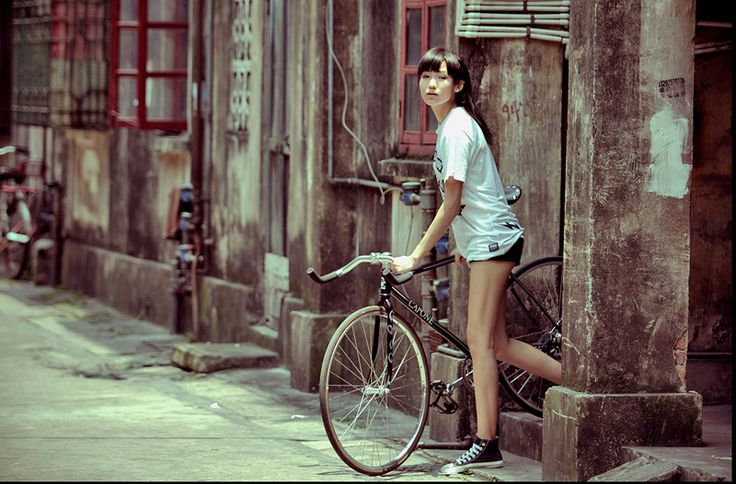 Girl + bike.  Awesome shot,  this looks like my town Suzhou! or maybe Shanghai
