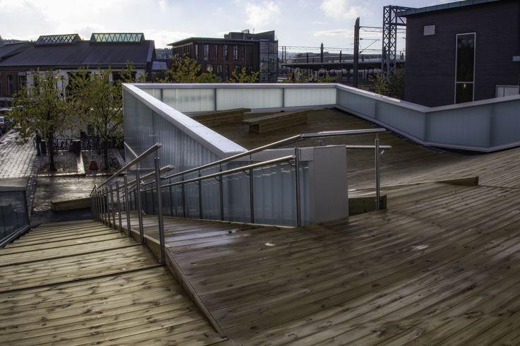 Wooden rooftop terrace of Norwegian bicycle hotel by Various Architects. Handrails made of steel and u-glass. /  Tre takterrasse på norsk sykkelhotell av ulike arkitekter. Rekkverk av stål og u-glass.