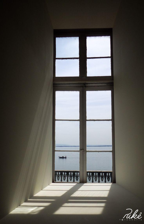 um barco visto através da janela duma das torres da Praça do Comércio