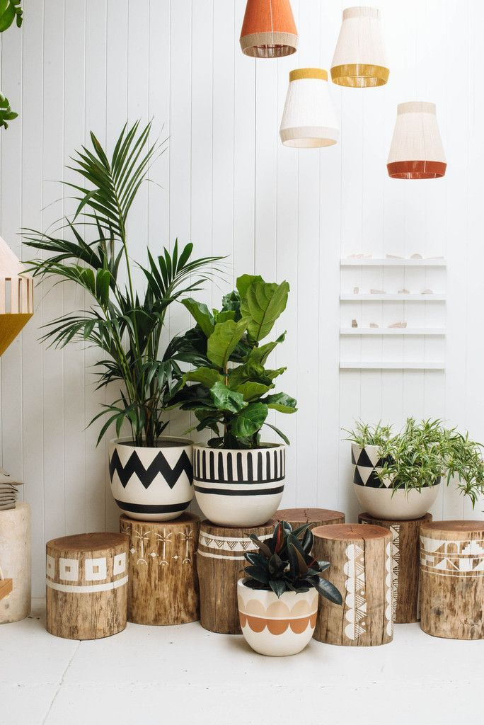 Beautiful corner with tribal style pots and wooden logs stamped in white …