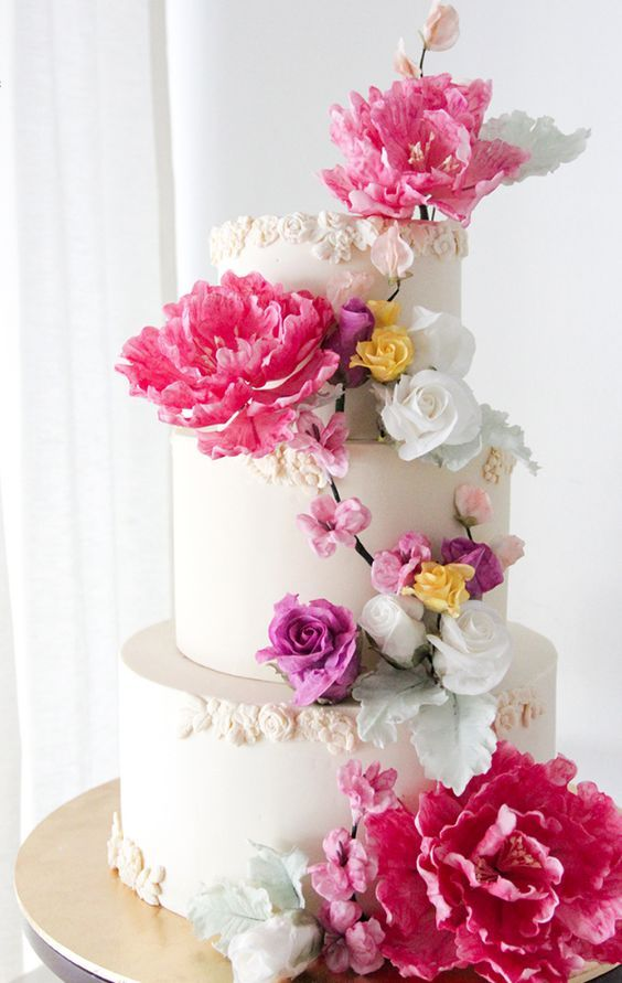 Chic three tier wedding cake with bold pink flowers;  Featured Cake: Winifred Kristé Cake