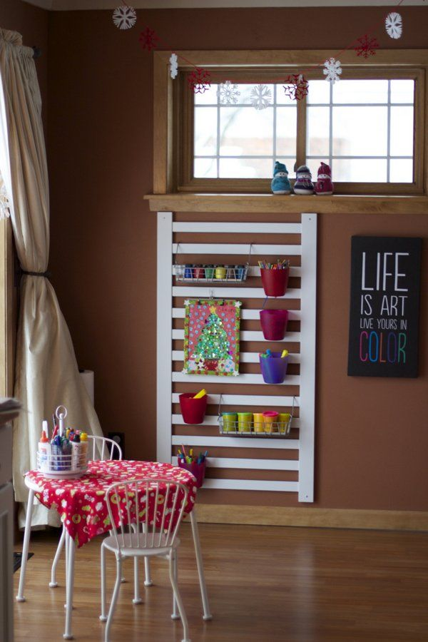 Repurposed crib rail and hanging storage containers. This would go good next to his art desk to hold all his pencils and other tools..