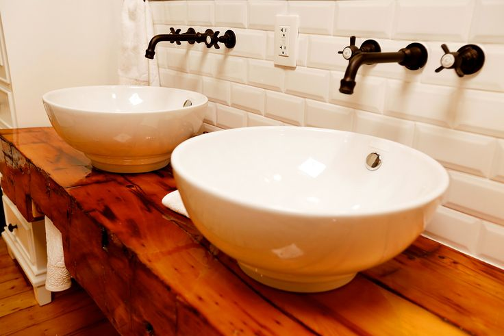 Modern vessel-style sinks pair beautifully with the reclaimed barn beam vanity counter! Designed and built by Paul Lafrance Design.