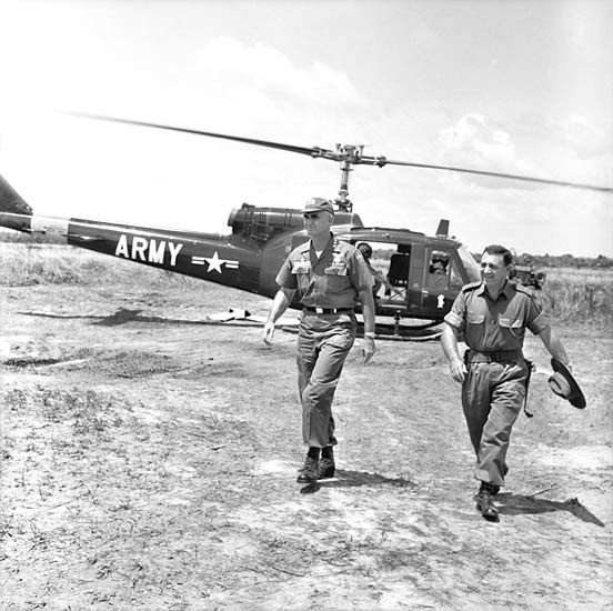 General William Westmoreland, Commander, US Military Assistance Command Vietnam (left) and Lieutenant Colonel Ivan 'Lou' Brumfield, Commanding Officer of 1RAR, leave a US army helicopter before inspecting IRAR's defences at Bien Hoa airbase, June 1965.