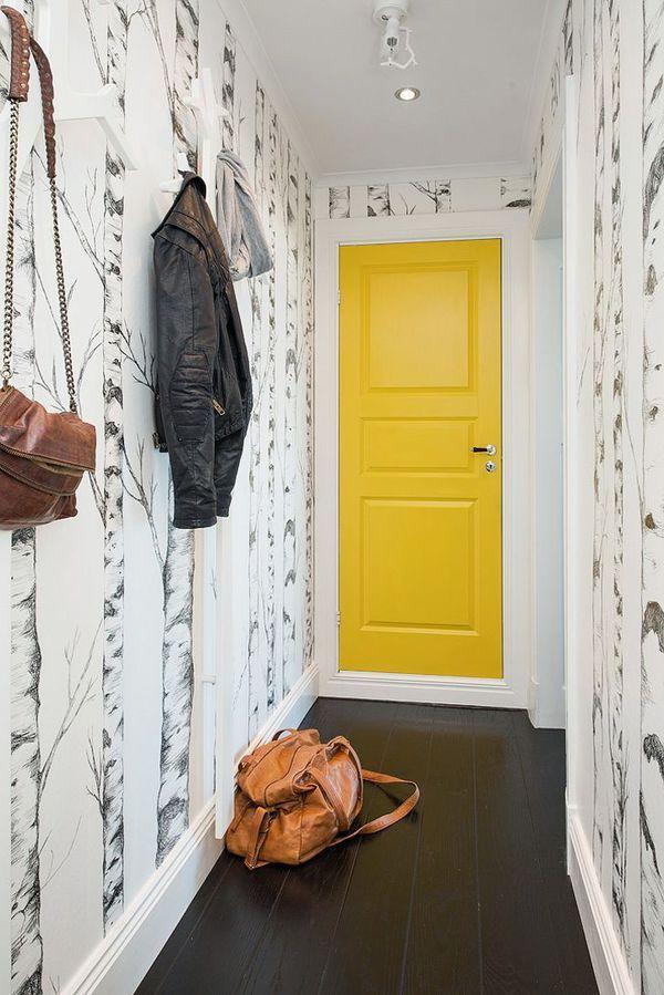 Porte jaune au bout d'un long couloir avec murs habillés de papier peint imprimé.