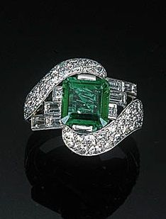 An Art Deco Emerald and Diamond Ring. The central square-cut emerald weighing 2.09 carats within graduated baguette-cut side details and pavé-set scrolled shoulders to the plain hoop. Stamped H&Co.