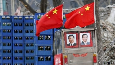 Portraits of Chinese President Hu Jintao (L) and Premier Wen Jiabao are displayed on a tricycle at a demolished residential site where new skyscrapers will be built in Beijing, 18 February  2013