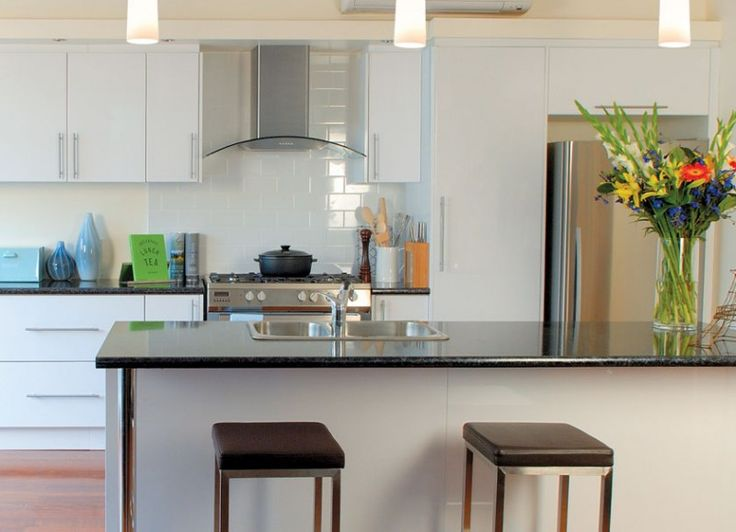 Galley style kitchen with a kitchen island. Black Granite laminate benchtops... +kaboodle kitchen