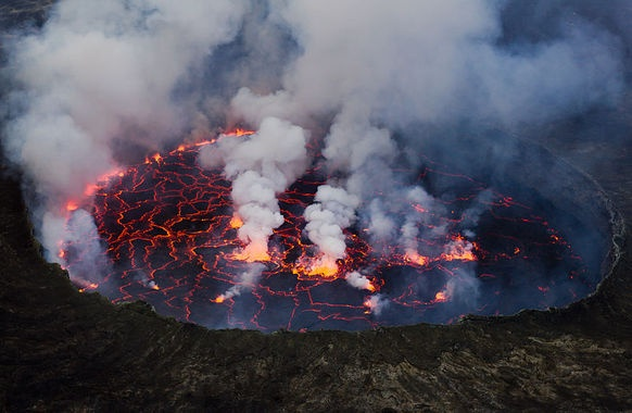 Lava Lake at Nyiragongo Volcano:    Located inside Virunga National Park about 20 km. North of Goma, Mount Nyiragongo is currently still active, its last deadly eruption taking 147 lives in 2002. Its activity is, for now, being confined to the crater, where the lake of lava is slowly rising once more. Unlike your average lava flow, the unique presence of an alkali-rich volcanic rock, melilite nephelinite, creates a highly fluid consistency.