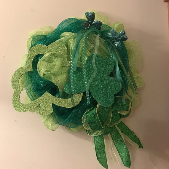 This Shamrock gem is sparkly and is the perfect lucky charm to add to your entry way or wall. Green and lime deco mesh securely fastened with zip ties for a sturdy outdoor quality. Accents include a glittered hollow shamrock in line and a smaller green solid one. A sheer and shamrock ribbon bow and festive accents. Measures 22 wide for great door, window or wall coverage.