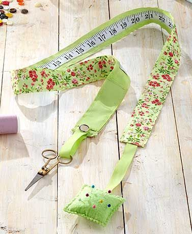 """This Neck Sewing Caddy keeps all the necessary tools on hand for any given project. This strip of fabric has a 35"""" measuring tape on one side and a striking pat"""