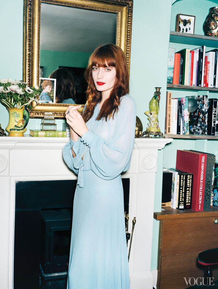 Wlech, in a silk Saint Laurent by Hedi Slimane dress, near her nineteenth-century English mirror and Victorian fireplace in the living room.