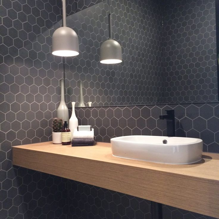 Dark grey tiles with contrasting lighter grey grout against light wood and white sink.