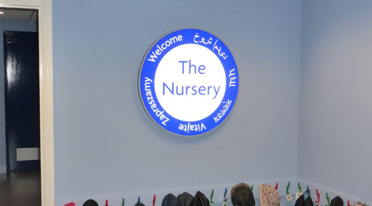 'The Nursery' circular lightbox sign installed to nursery entrance in a primary school. Welcome your students, parents, staff and visitors with a unique bespoke sign suited to your space. By space3.co.uk