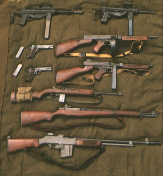 """U.S. Army WWII weapons. (Top, bottom, L to Rt). Two .45cal M3 """"grease guns"""". Two .45cal 1911 pistols, two .45 cal Thompson SMG's, .30 cal M1 carbine, .30-06cal M1 Garand rifle, & .30-06cal BAR rifle."""