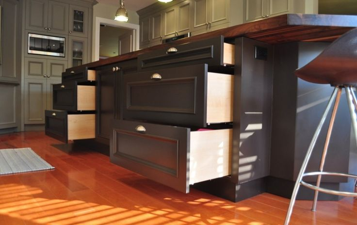This dark espresso island full of cabinets and drawers adds much needed storage to this beautiful trendy grey kitchen.