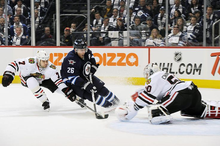 Chicago Blackhawks at Winnipeg Jets - Game W 5-1- 11/02/2013 Blake Wheeler #26 of the Winnipeg Jets cuts to the front of the net as Brent Seabrook #7 and goaltender Corey Crawford #50 of the Chicago Blackhawks defend at MTS Centre in Winnipeg, Manitoba, Canada.  (Photo by Lance Thomson/NHLI via Getty Images)