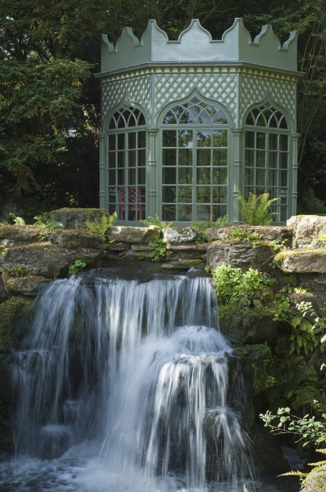 The garden at Woolbeding, West Sussex with Gothic folly in the background a very natural looking water feature in the foreground.