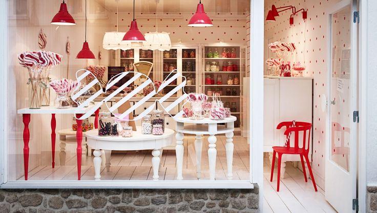 Un negozio di caramelle con tavoli e soluzioni nei colori bianco e rosso