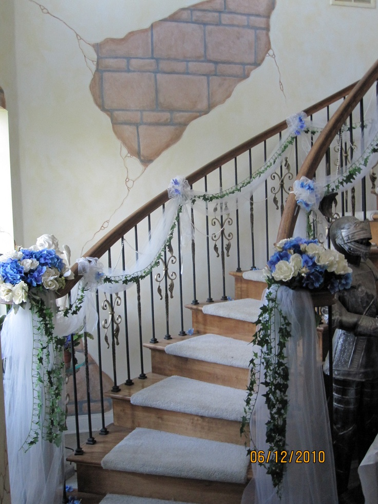 Sis-n-law's wedding staircase; at the castle, the tulle and ivy were already tied. We just added blue silk hydrangeas and white roses to the curl of the lower banister and sprinkled hydrangea petal up the knots.
