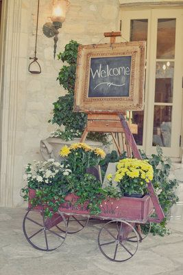 love the chalkboard sign and wagon with potted flowers to make the guests feel welcome!!