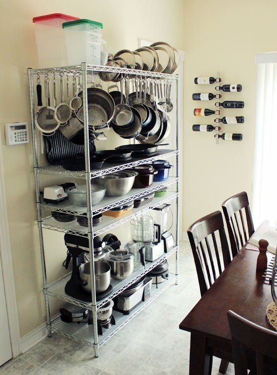 Pots and pans hanging on a wire rack- what a great idea for INSIDE the pantry- I would not want all the visual clutter in open view...