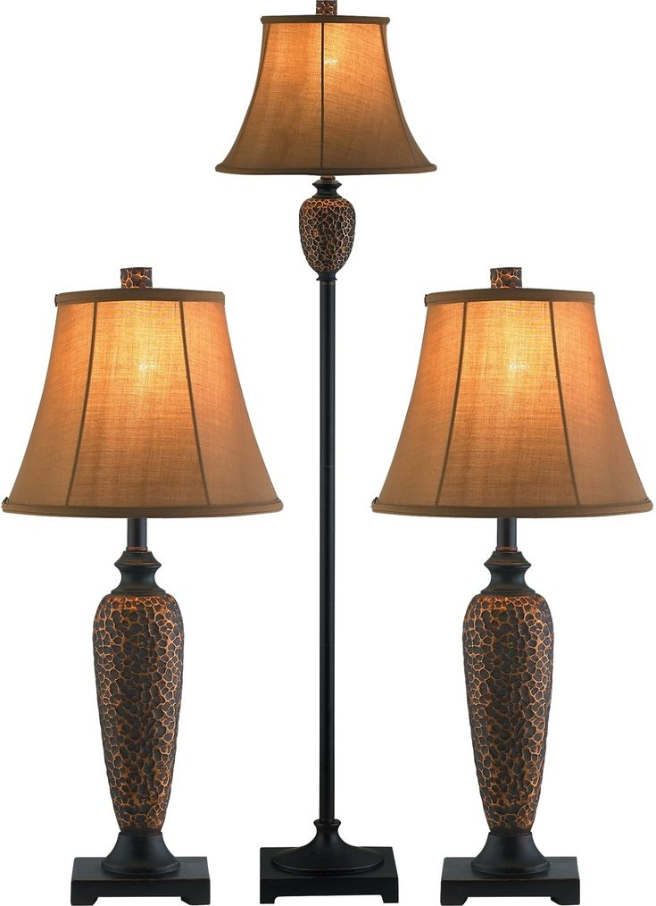 These beautifully textured table and floor lamps feature a hammered bronze poly resin base with a  tri-socket lamp with a beautiful soft back bell shaped shade in an earthy brown. These lovely transitional lamps work well in a variety of decors. Use them with neutral golds and browns or let it warm up a cool green or blue room.