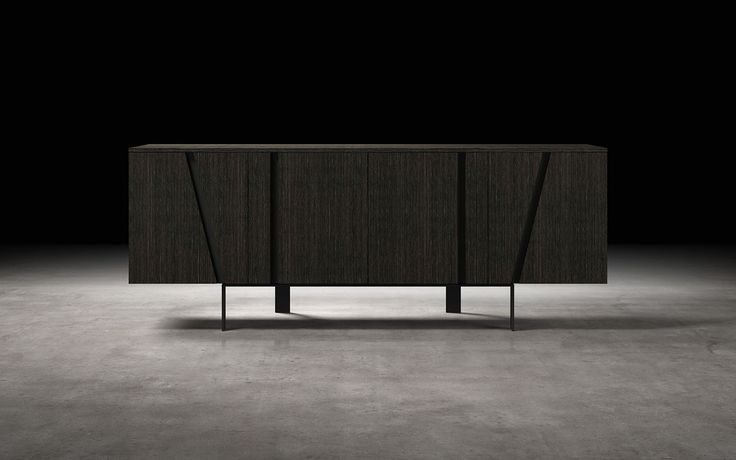 Angled cut-outs accent the wood grain of the Mott Sideboard's body, also serving as hidden handles for easily opening the buffet's two sets of double doors. Inside, a total of ten shelves and two smooth-gliding drawers offer plenty of storage space for your flatware and other dining room needs. The low-profile sideboard sits on a black powder coated base with feet splayed in rotating directions for a quintessential contemporary look. Contrasting interior colors present a cool modern a...
